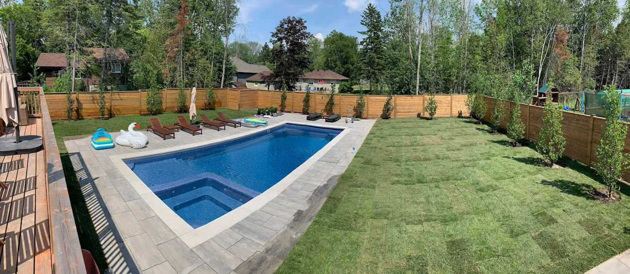 Finished fiberglass pool installation with a beautiful yard