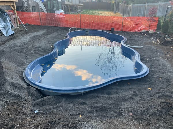 A backyard pool installation in progress