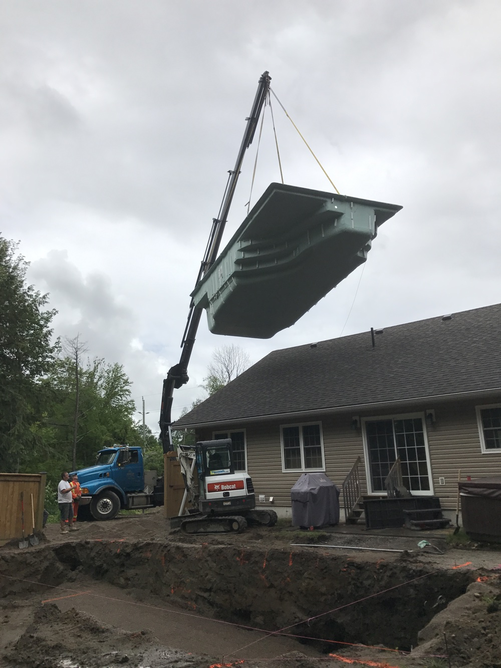 Crane lifting a fiberglass pool over a house in Barrie, Ontario