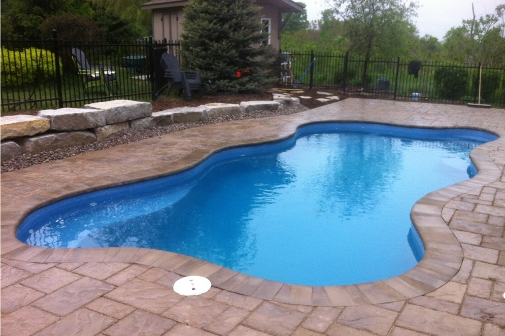 Beautiful fiberglass swimming pool with stone patio